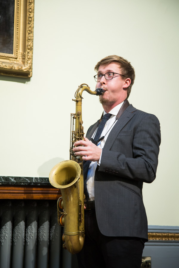 Wedding guest playing saxaphone during the wedding ceremony at Cutlers' Hall Sheffield