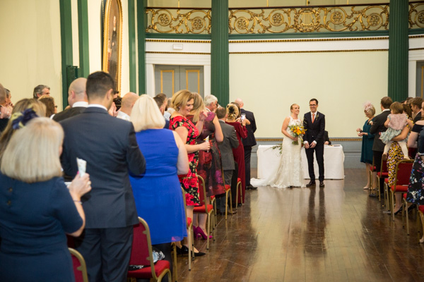 Bride and groom face their wedding guests at Cutlers' Hall Sheffield