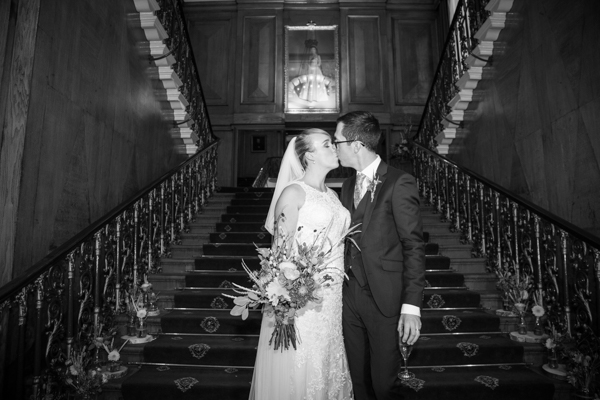 Bride and groom kiss on the grand staircase at Cutlers' Hall Sheffield