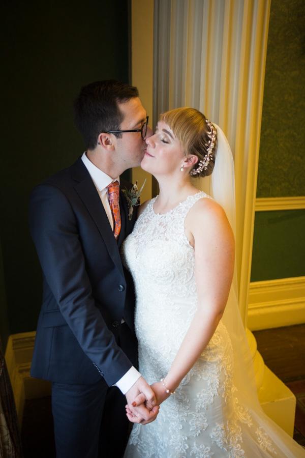 Groom kissing brides cheek at Cutlers' Hall Sheffield