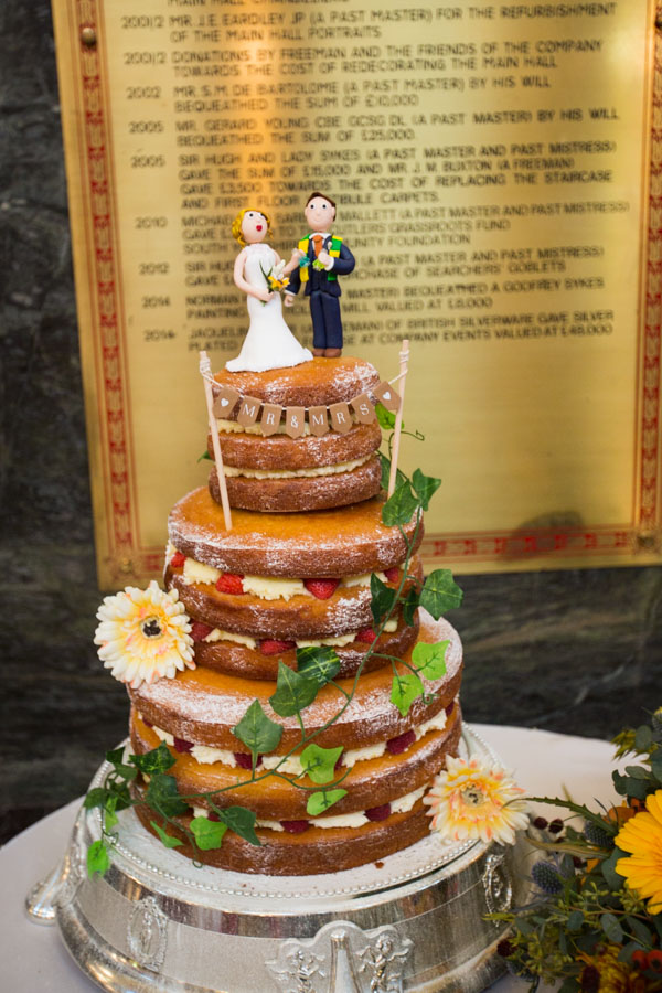Naked wedding cake with bespoke handmade cake topper of bride and groom