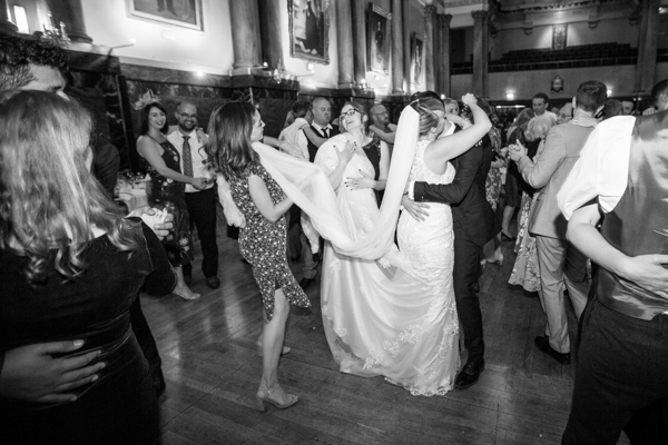 Guests holding the brides dress while she dances at Cutlers' Hall Sheffield