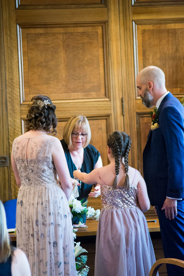 Flower girl giving the registrar the wedding bands Barnsley Town Hall Wedding