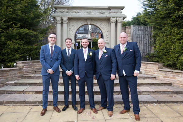 Groomsmen standing together outside the entrance to the secret garden at Holiday Inn Barnsley