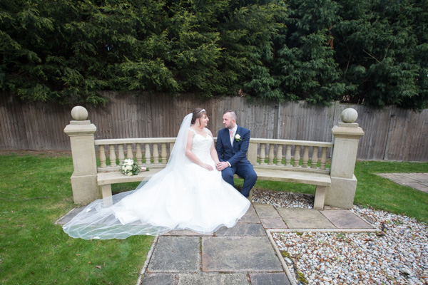 Bride and Groom sitting on a stone bench at the secret garden at Holiday Inn Barnsley