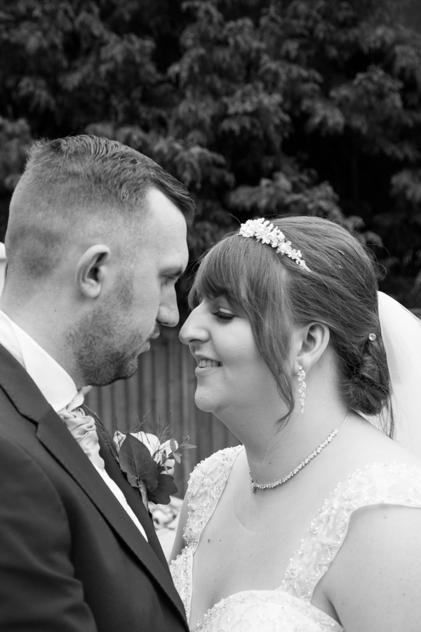 Bride and Groom look at each other in the secret garden at Holiday Inn Barnsley