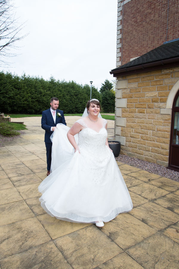 Groom holding brides dress at Holiday Inn Barnsley