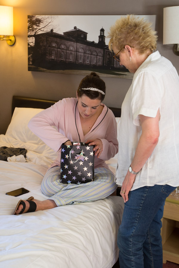 Bride opening a gift bag on the morning of her wedding at The Rockingham Arms