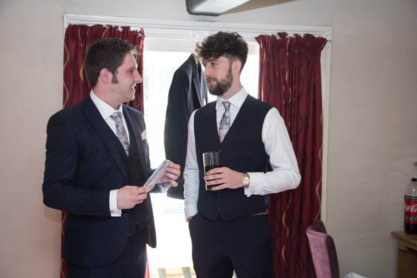 Groomsmen talking to each other at The Rockingham Arms