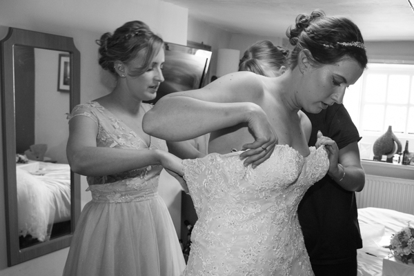 Bridesmaids helping the bride get ready at The Rockingham Arms