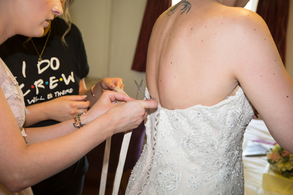 Bridesmaids fastening the wedding dress at The Rockingham Arms Wentworth
