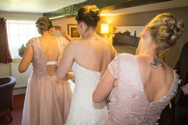 Bridal party fastening dresses at The Rockingham Arms Wentworth