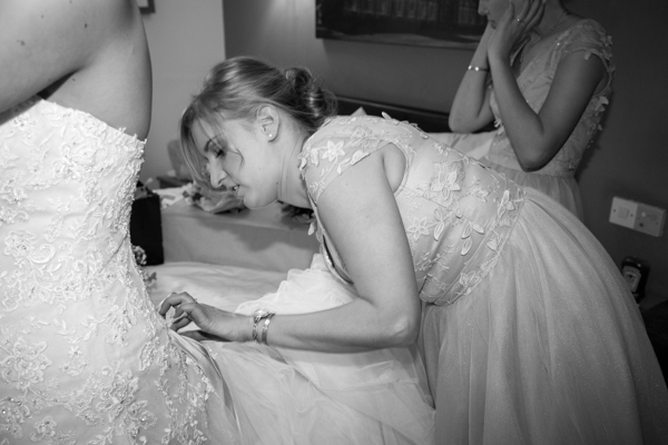 Bridesmaid fastening the wedding dress at The Rockingham Arms Wentworth