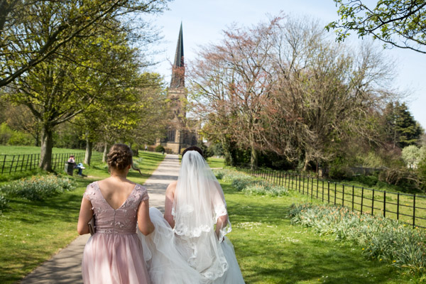 Bridesmaid holding Brides dress as they walk to Wentworth Church