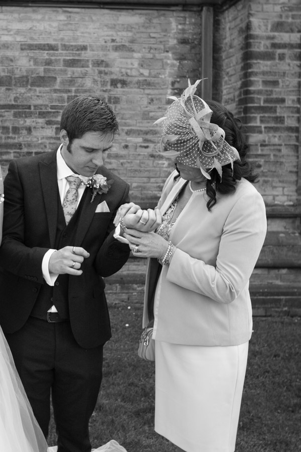 Mother of the Groom helps him with his watch outside Wentworth Church