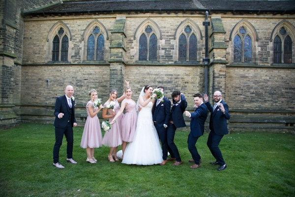 THe bridal party in a silly pose outside Wentworth Church