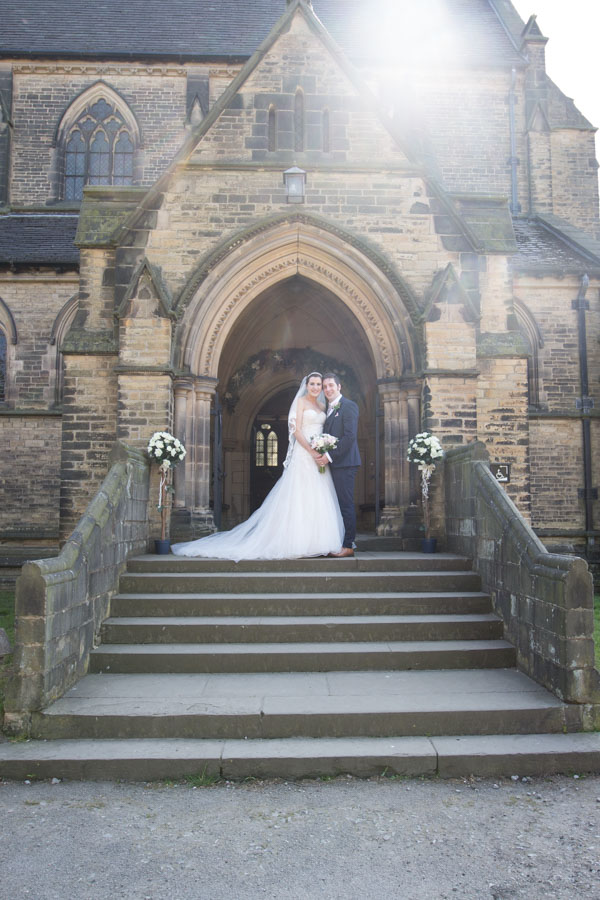 Bride and Groom stand on the steps outside Wentworth Church