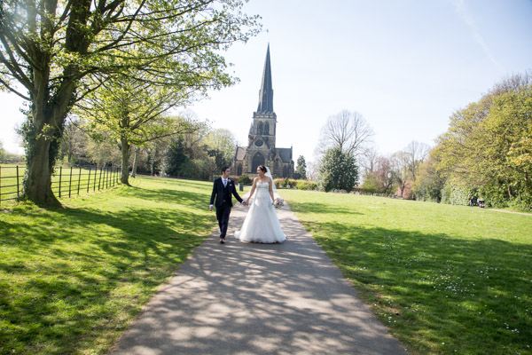Bride and groom holding hands and walking down the path outside Wentworth Church