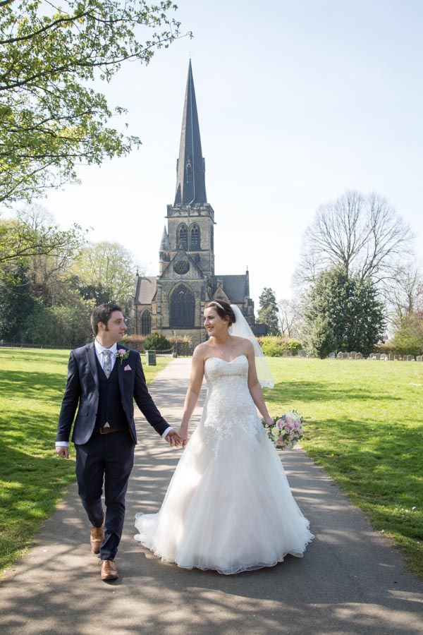 Bride and groom smiling at each other as they walk down the path outside Wentworth Church