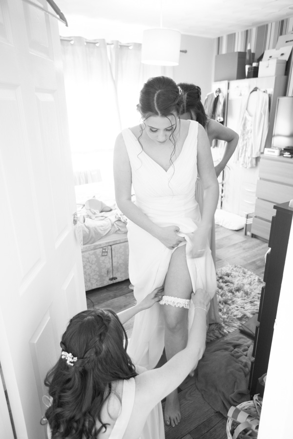 Bridesmaids helping bride get into her garter and wedding dress