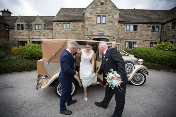 Bride to be getting out of the wedding car with help from her uncle