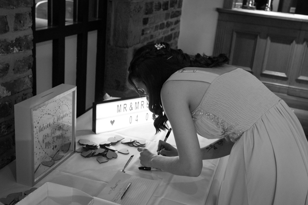 Bridesmaid writing in the guestbook at Tankersley Manor Hotel Wedding