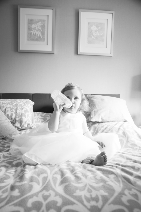 Flowergirl sitting on a bed drinking a bottle