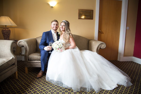 Bride and Groom sitting on a sofa at Holiday Inn Barnsley Wedding