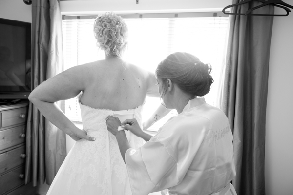 Bridesmaid helping to fasten the bridal gown