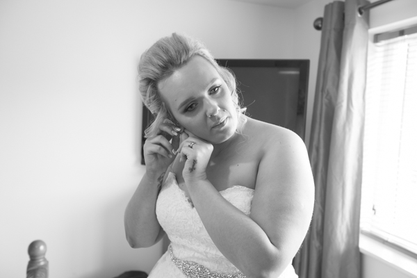 Bride putting in her earrings before the wedding