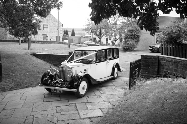 Bride arriving at wath church in a double r vintage car