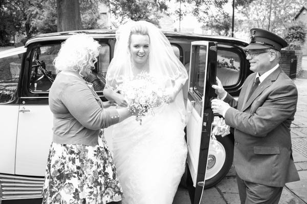 Bride getting out of a wedding car at Wath church
