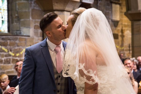 Bride and Groom kiss at Wath church
