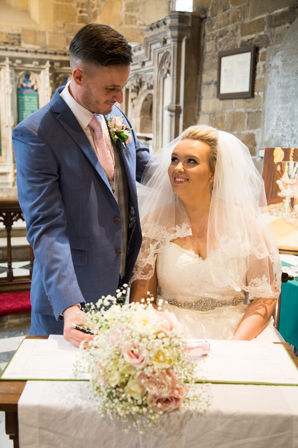Bride and Groom signing the register at Wath church