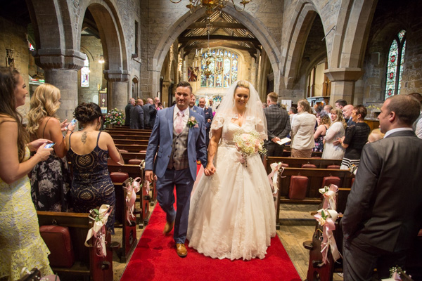 Bride and Groom walking back up the aisle at Wath church