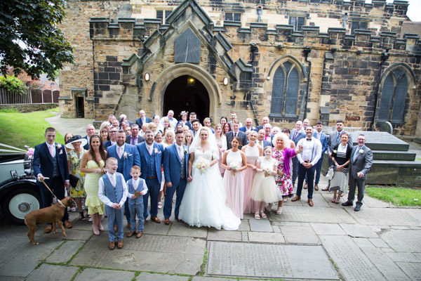 Full wedding party outside Wath church