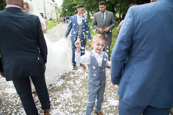 Page boy collecting confetti outside Wath church