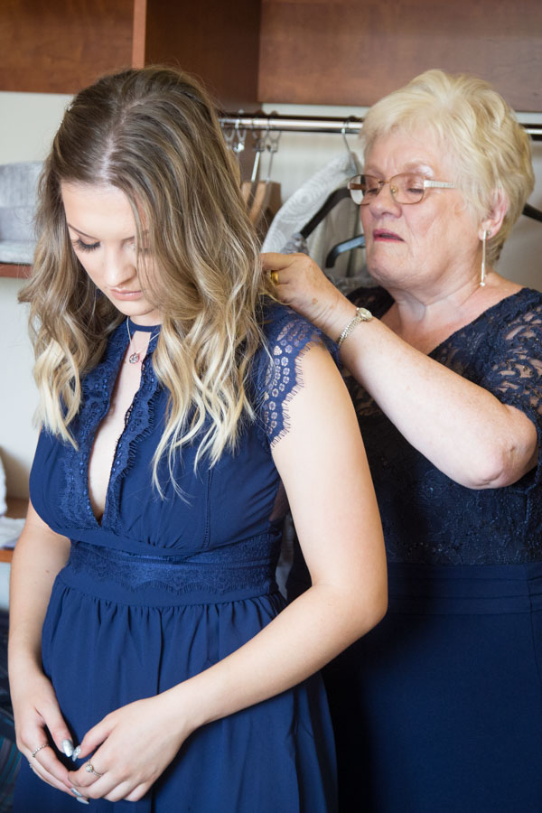 Bridesmaids helping each other fasten their dresses at Bluebell Banqueting Suite Barnsley Wedding