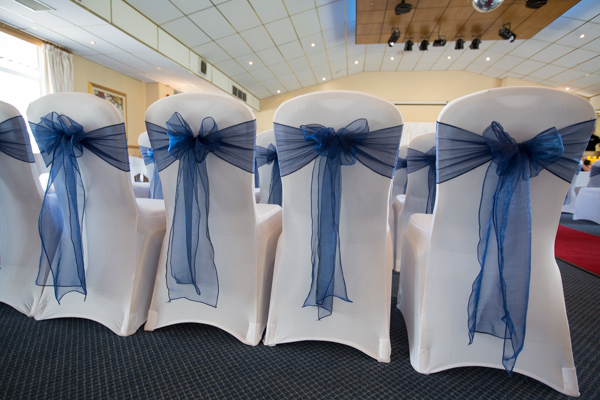 THe blue bows on the back of the chairs by All Trimmed Up at Bluebell Banqueting Suite Barnsley Wedding
