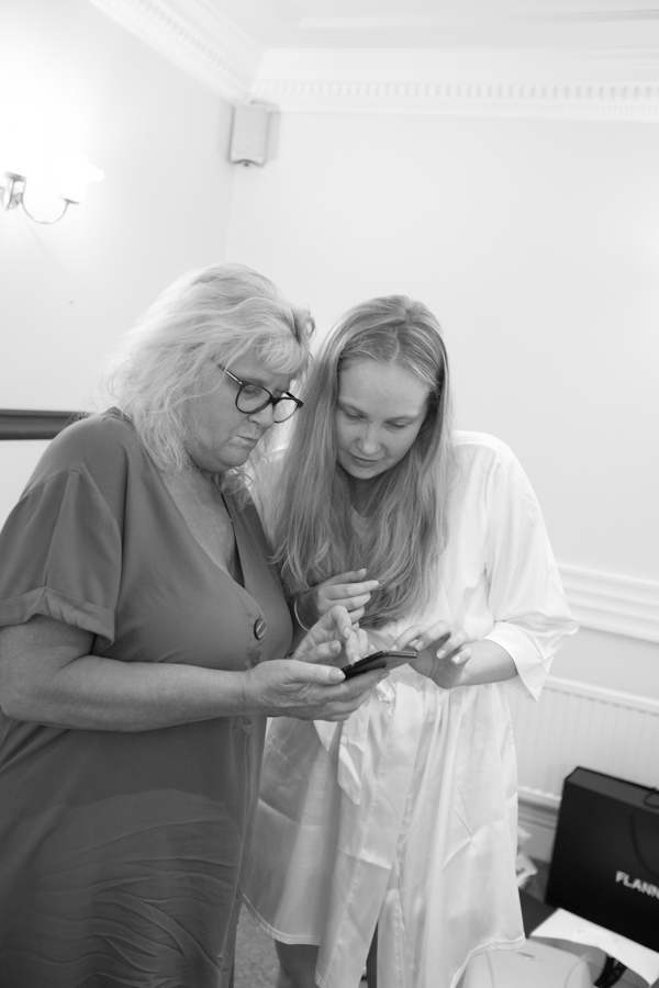 Bride and mother of the bride cheking their phone at Bagden Hall Hotel Wedding