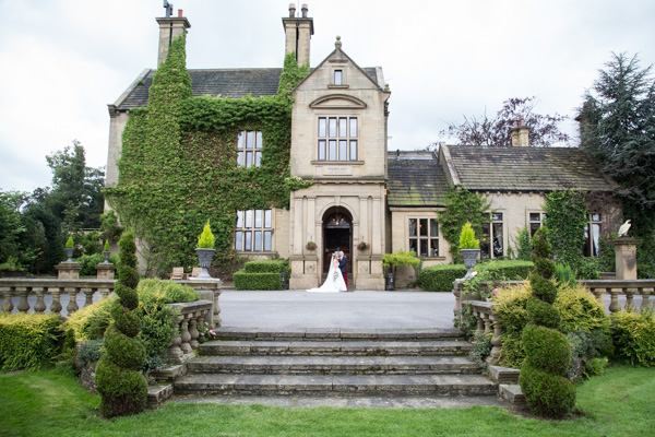 Wedding Day at Bagden Hall Hotel Huddersfield photography shows couple standing in front of the hotel surrounded by ivy