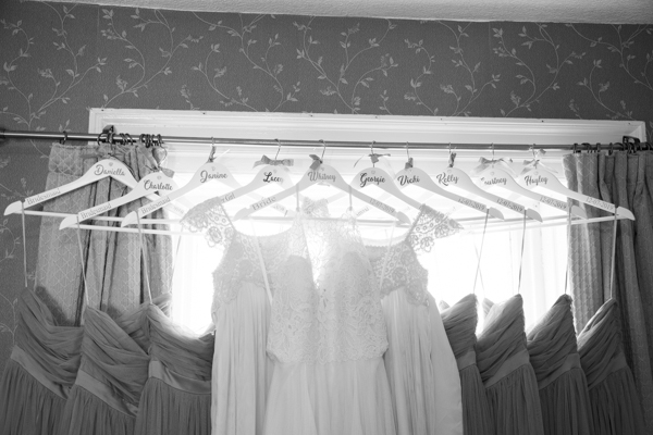 Bridesmaid dresses and wedding dress hung in a line with personalised hangers at Wortley Hall Wedding