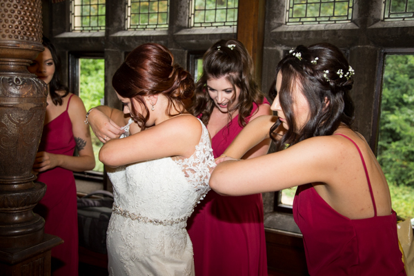 bridesmaids helping bride into her dress at Whitley Hall Hotel Wedding