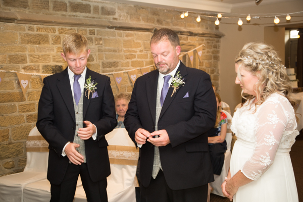 Bride and groom exchange rings at Whitley Hall Wedding