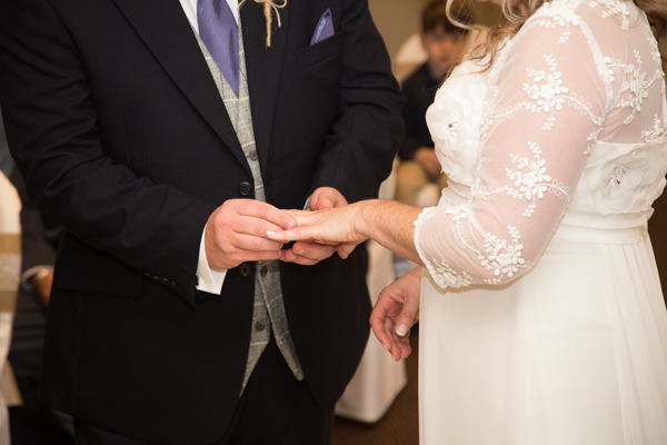 Bride and groom exchanging rings in the Parker Suite at Whitley Hall Wedding