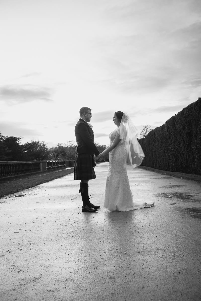 Bride and groom walking through Yorkshire Sculpture park on their wedding day
