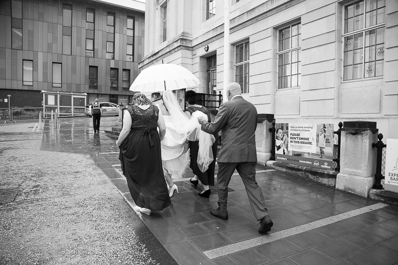 Bride walking to the ceremony at Barnsley Town Hall with the bridesmaids and her dad