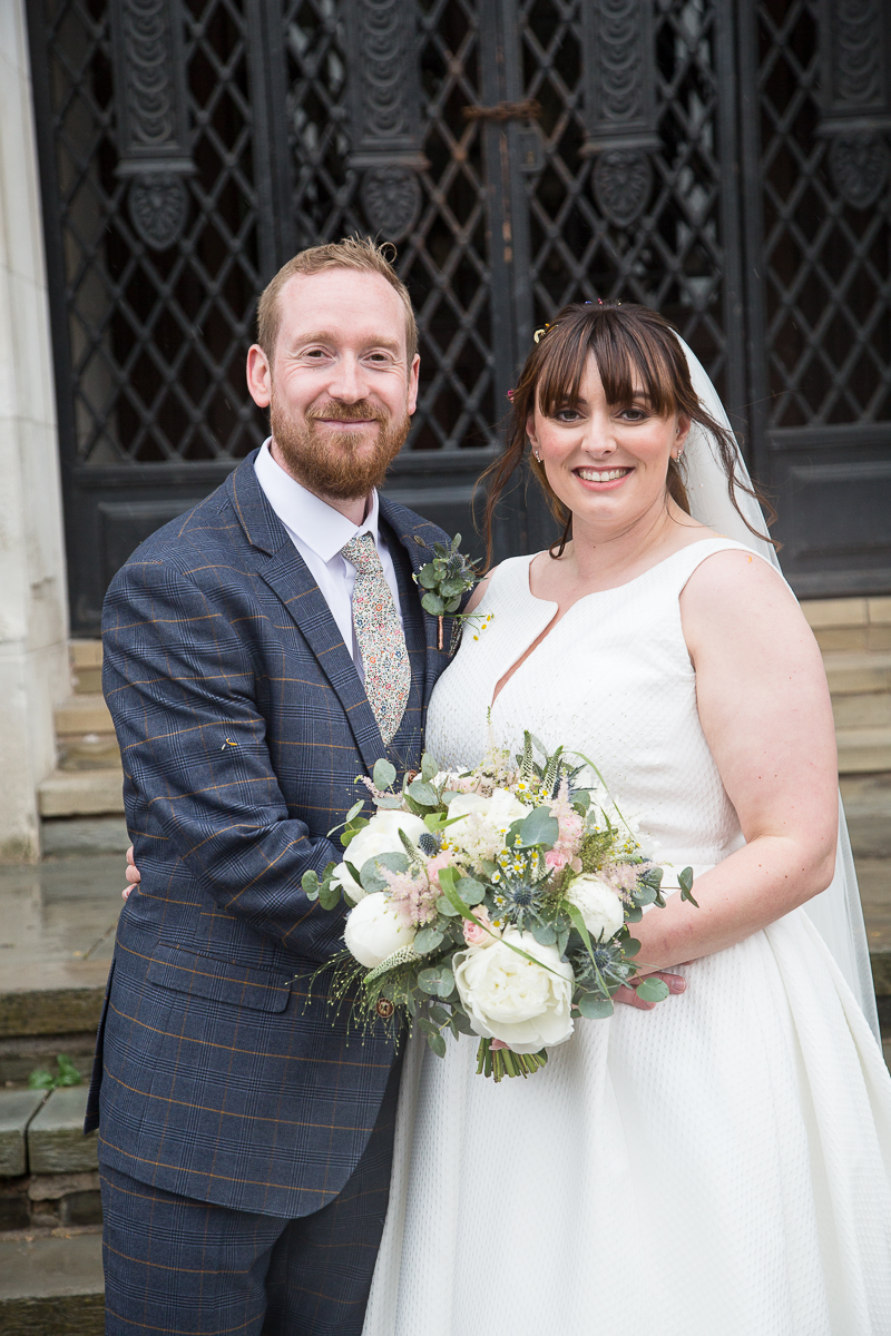 Bride and groom smiling in front of black iron doors at Barnsley Town Hall Wedding