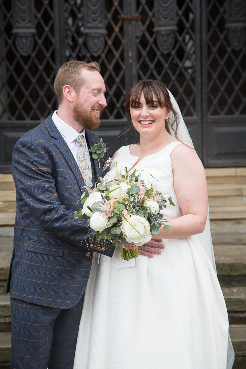 Bride and Groom smiling in front of the black iron gates at Barnsley Town Hall Wedding