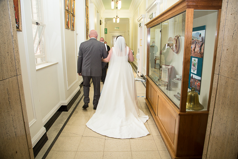 Bride walking to the ceremony room in Barnsley Town Hall with the father of the bride